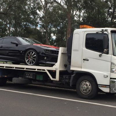 A towing truck with a black sedan car.